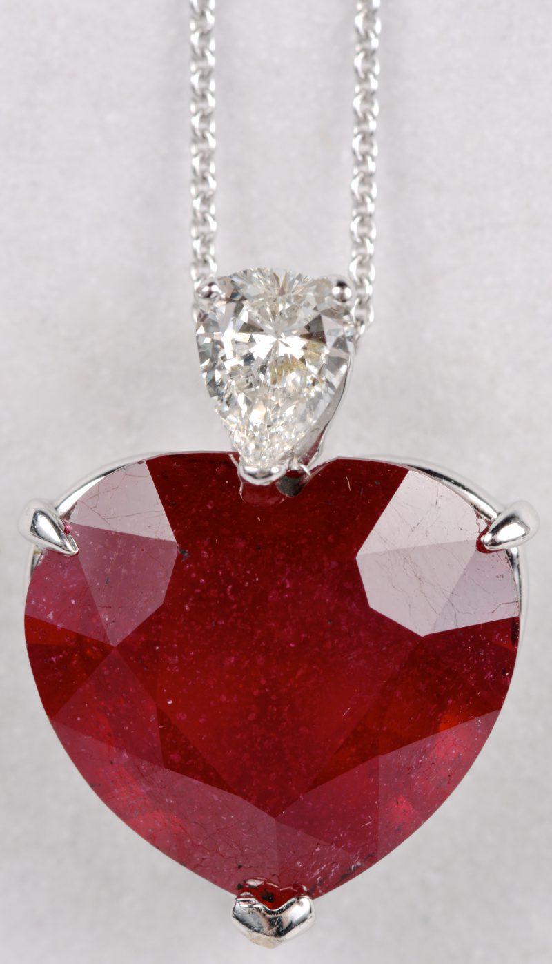Een 18 karaats wit gouden ketting met hanger in de vorm van een hart bezet met diamant van ± 0,40 ct. en een centrale robijn van ± 9 ct.