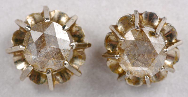 Twee verschillende 18 karaats geel gouden oorbellen bezet twee diamanten oude slijp met een gezamenlijk gewicht van ± 1 ct.
