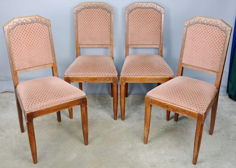 Een reeks van vier gebeeldhouwde stoelen.
