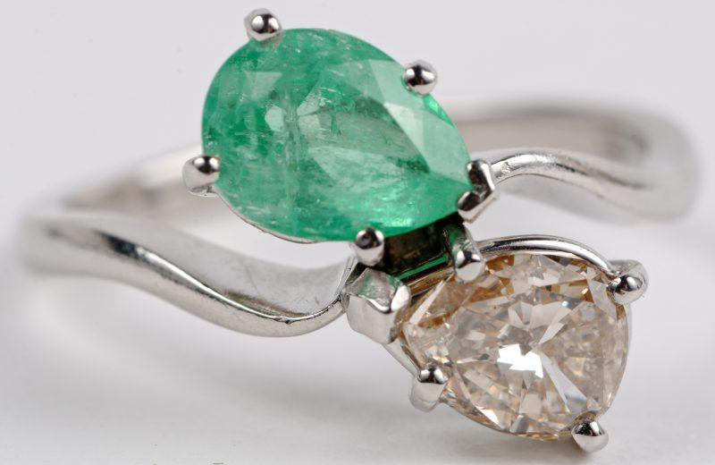 """""""Toi et Moi"""". Een 18 karaats wit gouden ring bezet met een diamant van ± 1ct. en een smaragd van ± 1 ct."""