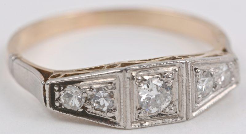 Een 18 karaats wit en geel gouden ring bezet met een briljanten met een gezamenlijk gewicht van ± 0,40 ct.