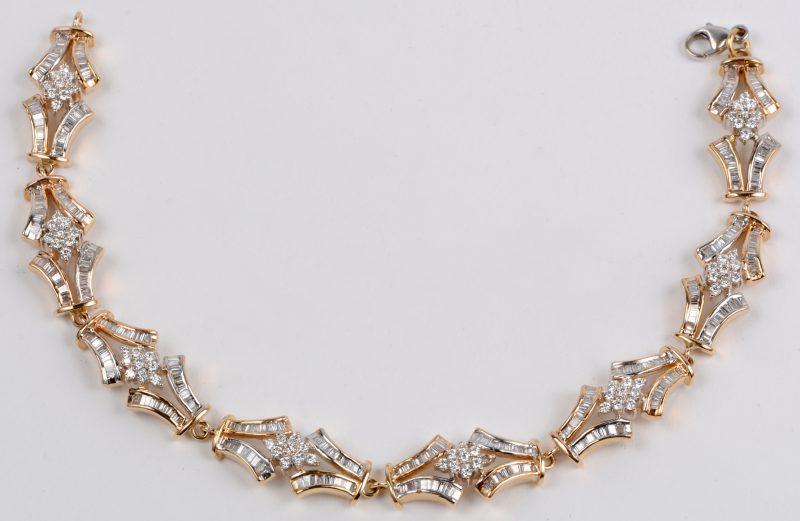Een 18 karaats wit en geel gouden armband bezet met diamanten en baguetten met een gezamenlijk gewicht van ± 7 ct.
