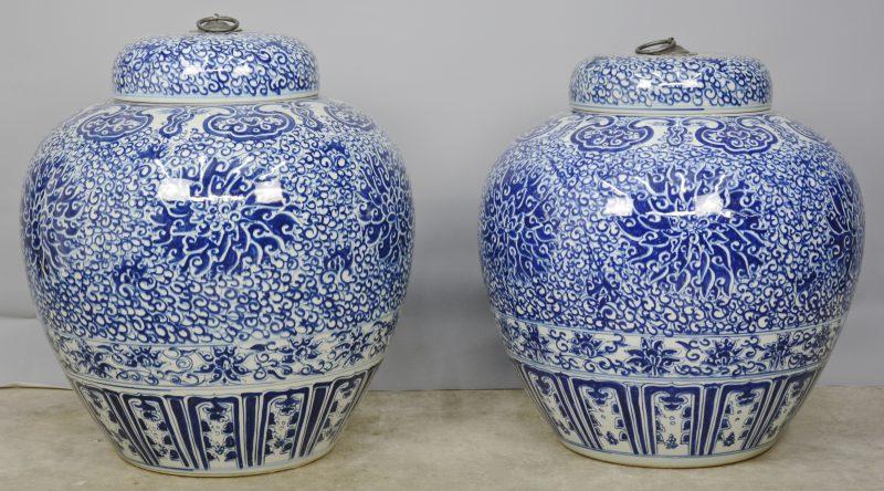 Twee grote gemberpotten van Chinees porselein, versierd met een blauw op wit decor met florale motieven.