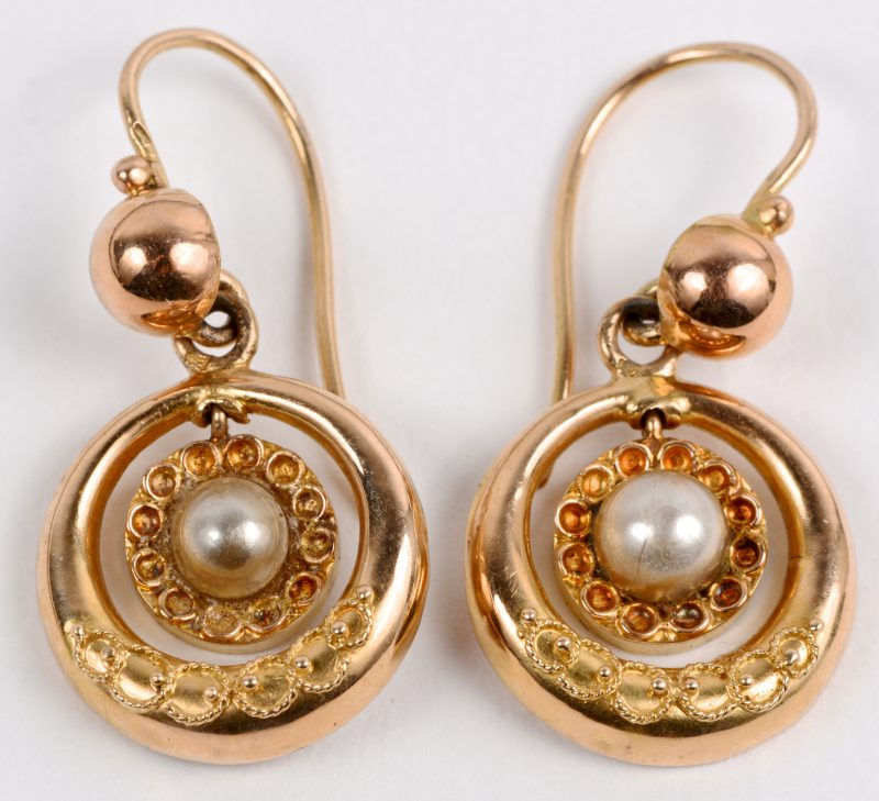 Een paar 14 karaats geel gouden oorbellen bezet met twee parels.