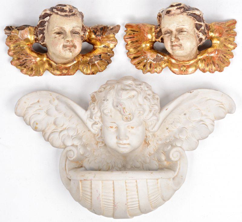 Twee engelenkopjes van gepolychromeerd en verguld hout en een wijwatervaatje van biscuit, eveneens getooid met een engelenkopje.