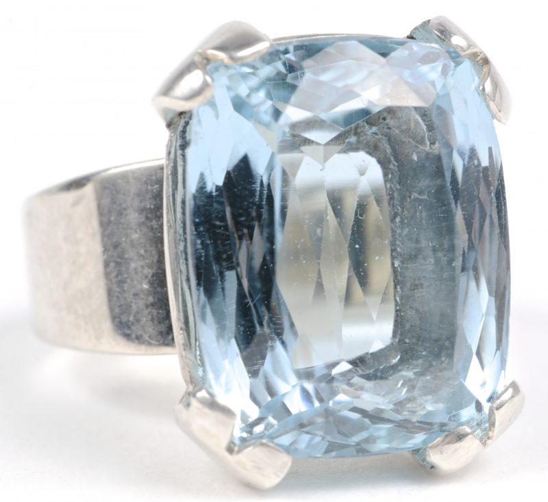 Een zilveren ring 900 ‰ bezet met een lichtblauwe kleursteen van ± 10 ct.