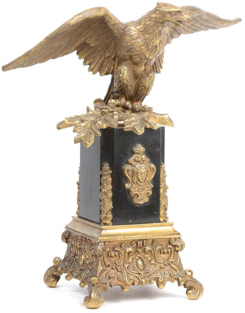 Een sierstuk van verguld brons in de vorm van een adelaar op een tak op een zuil van arduin. Omstreeks 1900.