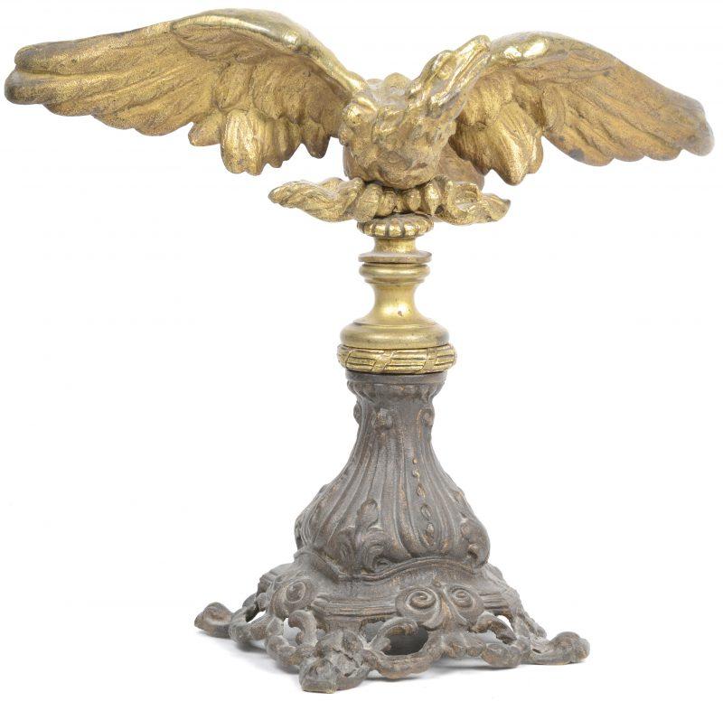 Een adelaar van verguld brons op voetstuk in barokke stijl.