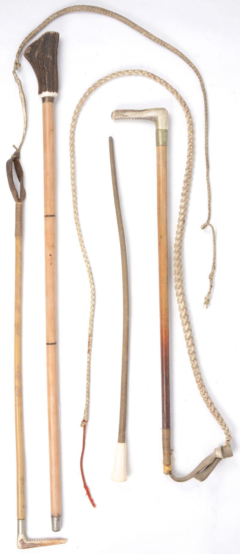 Een lot van twee wandelstokken en twee zwepen, waarbij drie met hoorn en één met ivoor.