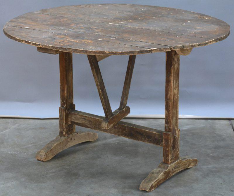 Een gebeitst houten ronde tafel met opklapbaar blad.