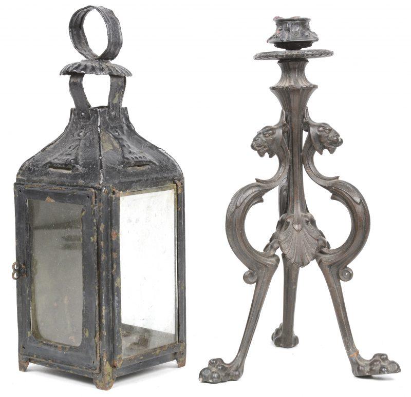 Een ijzeren lantaarntje en een kandelaar op drie voeten.