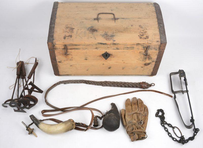 Een lot voorwerpen, bestaande uit een lederen ruitershandschoen, zes brandmerken, twee verschilende kruithoorns, een dierenklem en een zweepje. In houten kistje. (zonder sleutel)
