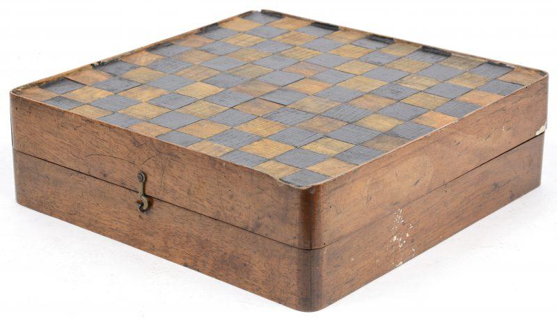 Een oude houten spellendoos (schaak-, dam-en triktrakbord) met gedraaide houten jetons (enkele manco's), teerlingen in lederen kokers en een dominoset van been en zwart hout. Slijtage.