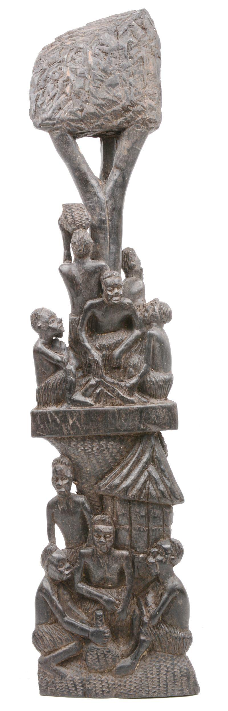 Een gesculpteerd Afrikaans houten beeld met diverse personages.
