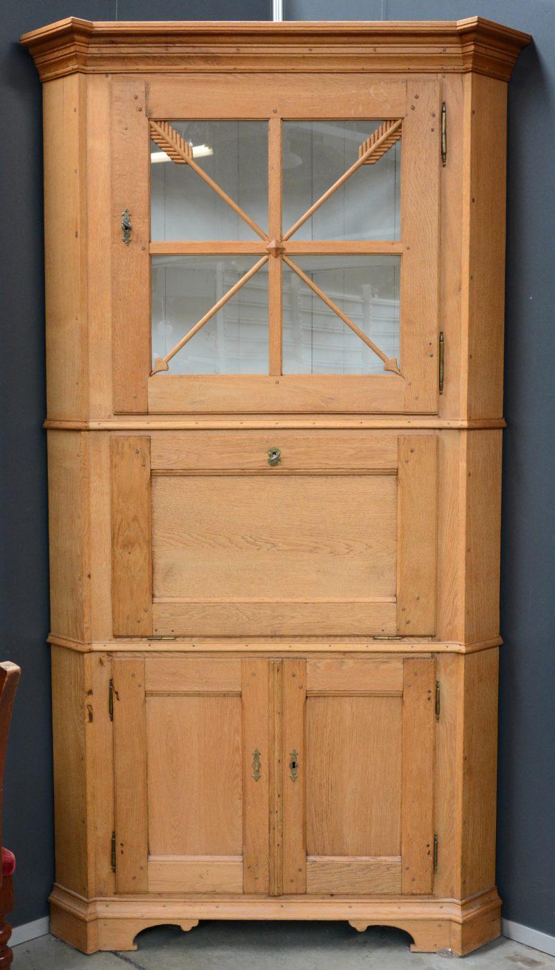 Een Gelderse hoekkast van blank eikenhout met twee paneeldeurtjes onderaan, een schijfblad en een gevitreerde deur bovenaan. Omstreeks 1820.