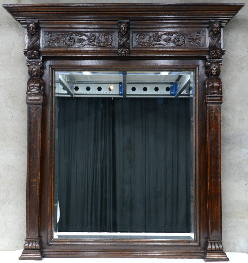 Een schouwspiegel van gebeeldhouwd eikenhout in Renaissancestijl.