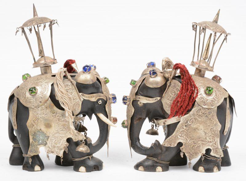 Een paar gebeeldhouwd ebbenhouten olifantjes met gedreven verzilverde versieringen met glazen kraaltjes.