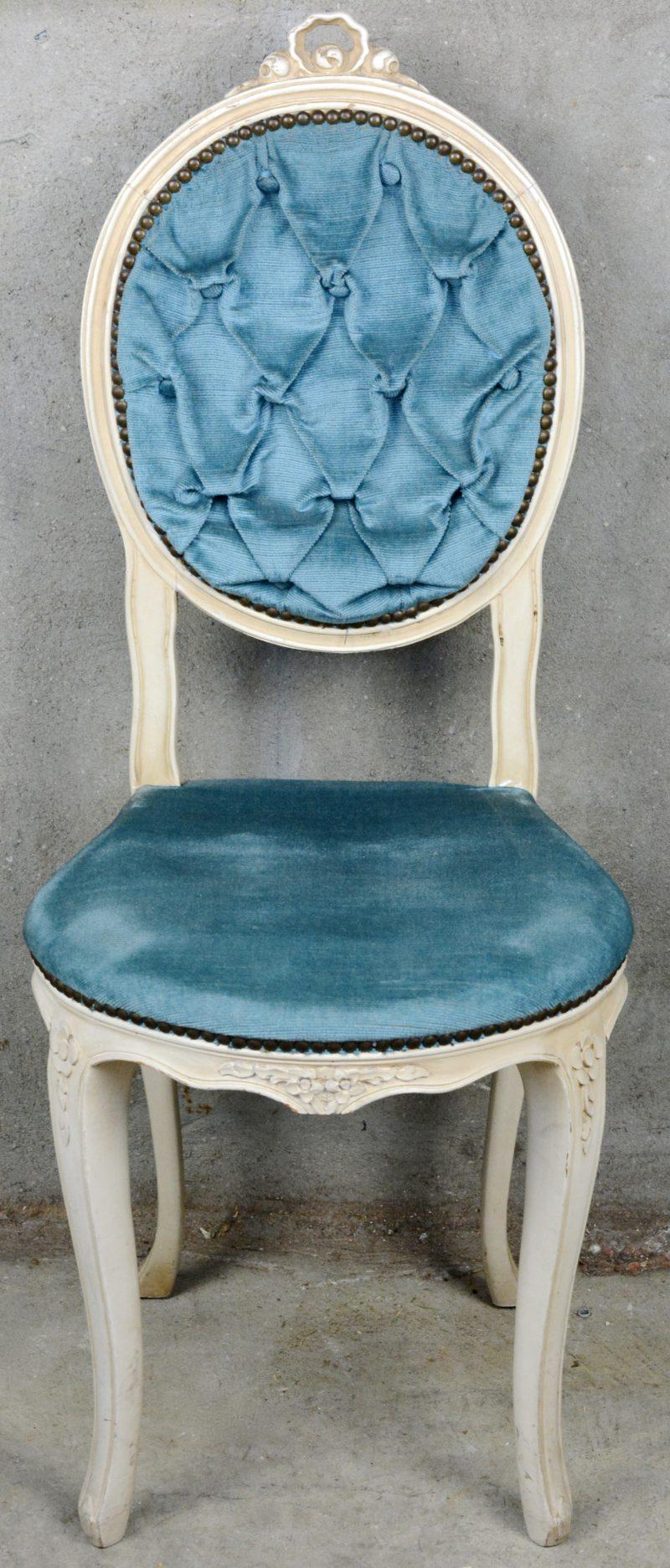 Een witgepatineerd boudoirstoeltje met blauw fluwelen bekleding.