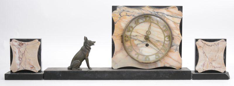 Een driedelig art deco klokstel van meersoortig marmer met een hondje van zamak. Restauratie en beschadiging aan een casolette.
