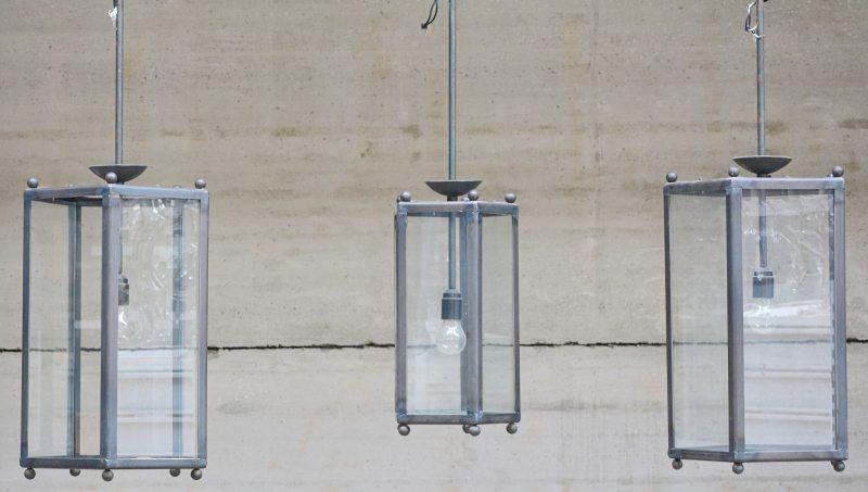Een lot van drie vijfhoekige lantaarns, waarbij één kleinere. Eén grote en de kleine met één ruitje manco.