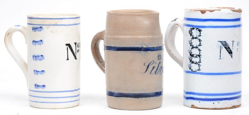 Een lot van drie bierpullen, waarbij twee aardewerken en één van steengoed.