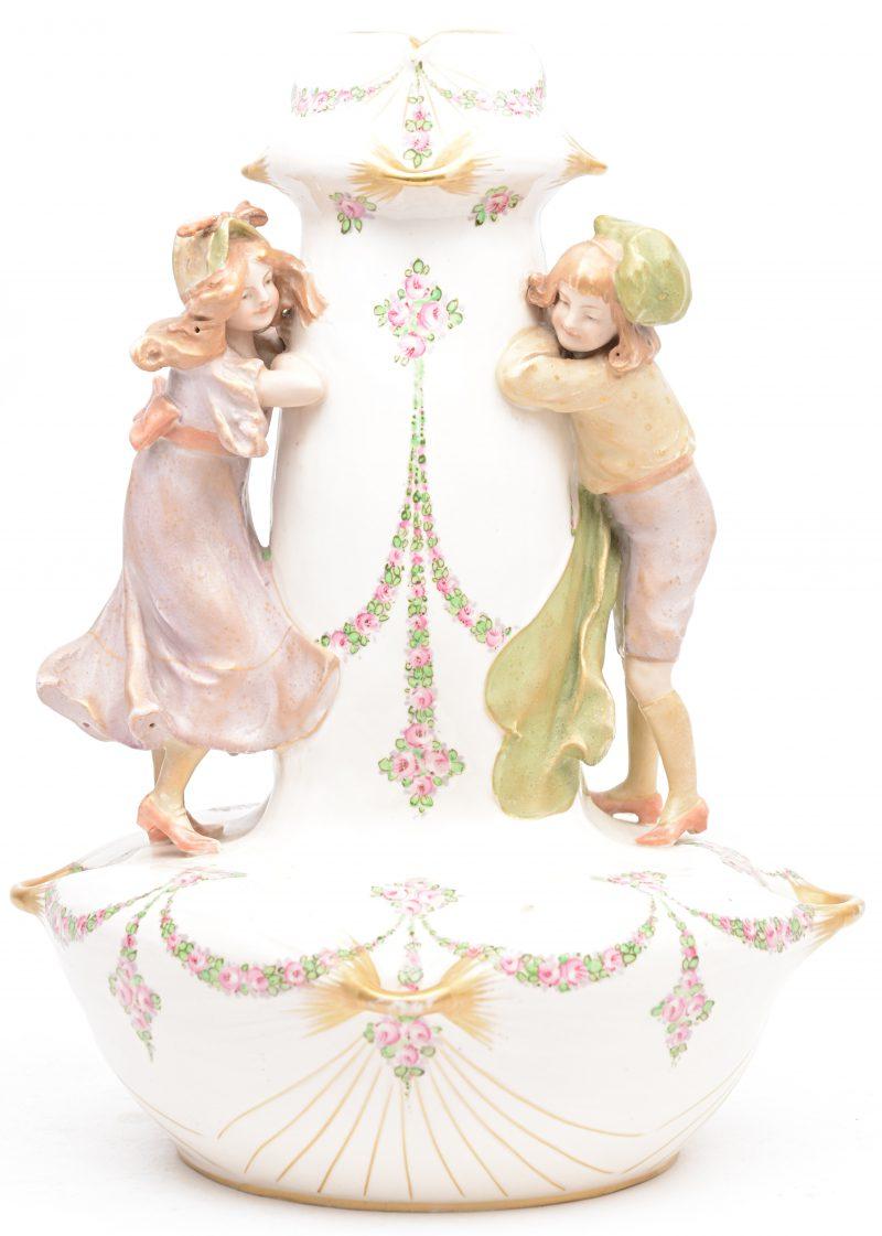 Een vaas van meerkleurig porselein, versierd met twee spelende meisjes. Onderaan gemerkt. Nummer 1321.