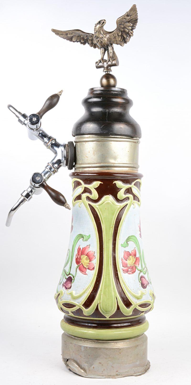 Een aardewerken tapkraan met meerkleurig bloemendecor, bovenaan getooid met een adelaar. Tijdperk Art nouveau. (Kranen recenter).