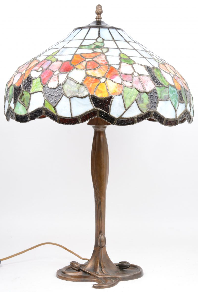 Een bronzen lampvoet met een kap van glas inlood in de geest van Tiffany.