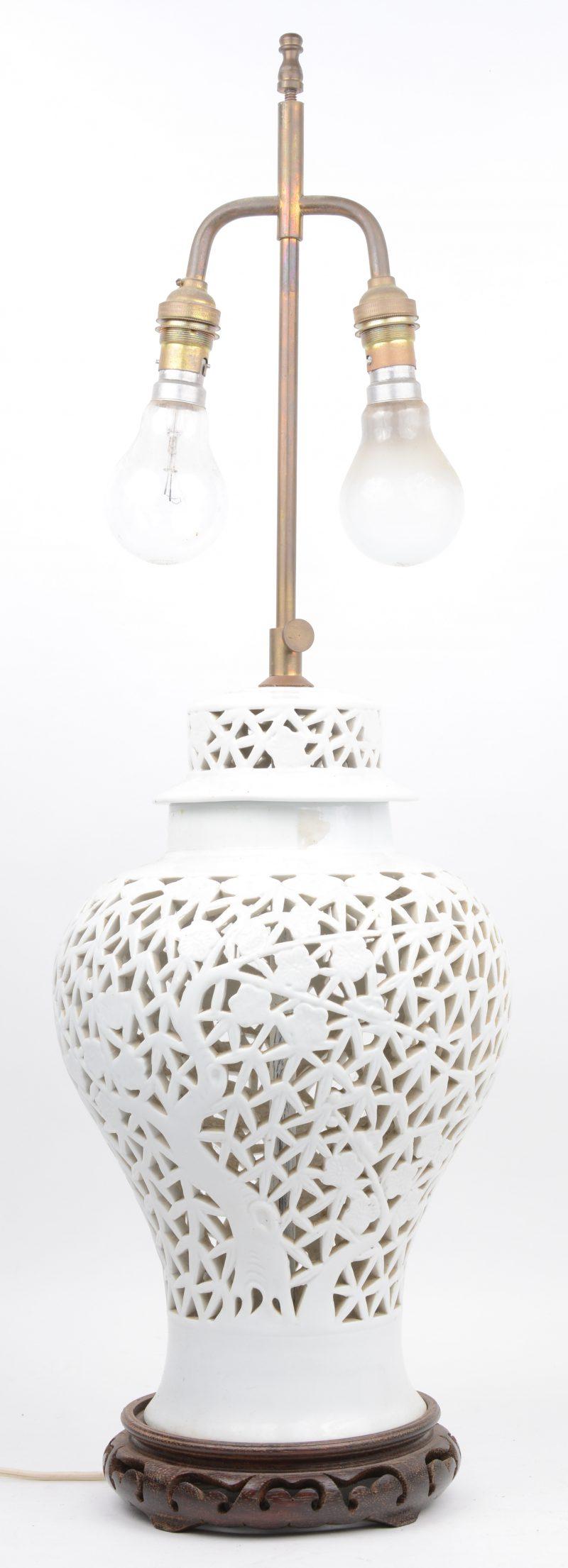 Een lampvoet van opengwerkt wit porselein.