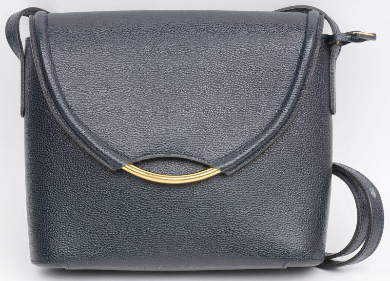 Een donkerblauwe schoudertas met drukknop in gekorreld leder, gevoerd met daim. Met originele draagtas.