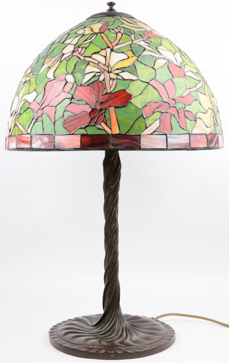 Een schemerlamp op getorste bronzen voet met kap van glas in lood in de stijl van Tiffany.