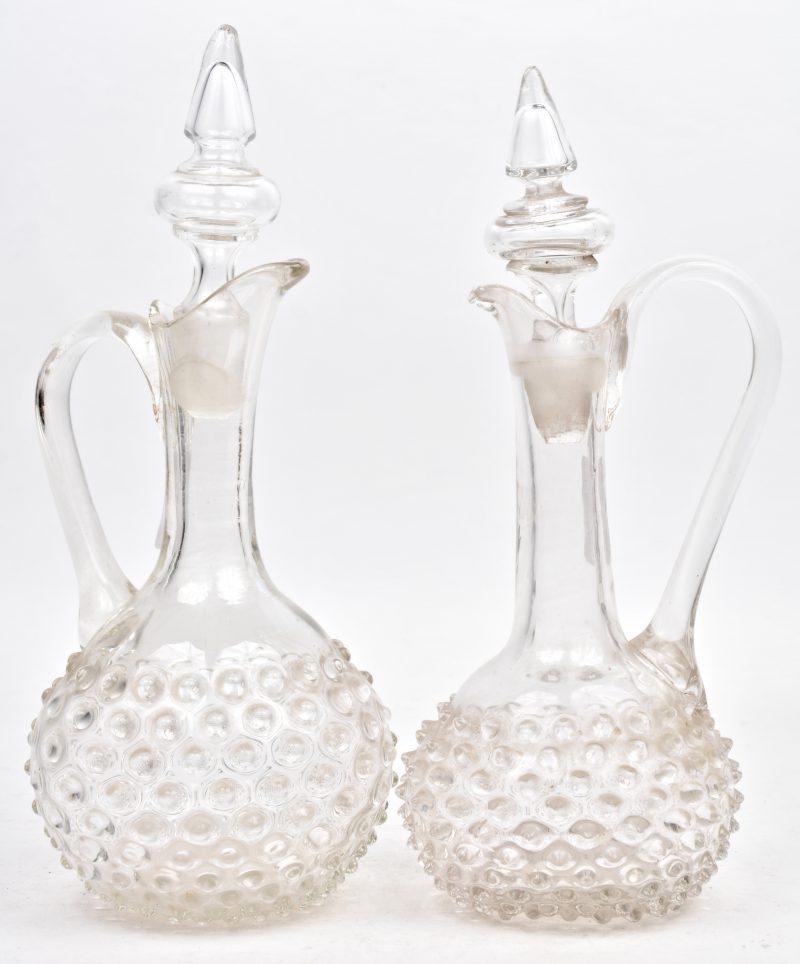 Een paar antieke mondgeblazen kleurloos glazen karaffen.