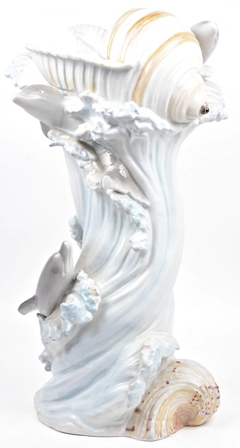 Een meerkleurig porseleinen siervaas in de vorm van een golf met schelpen en dolfijnen.