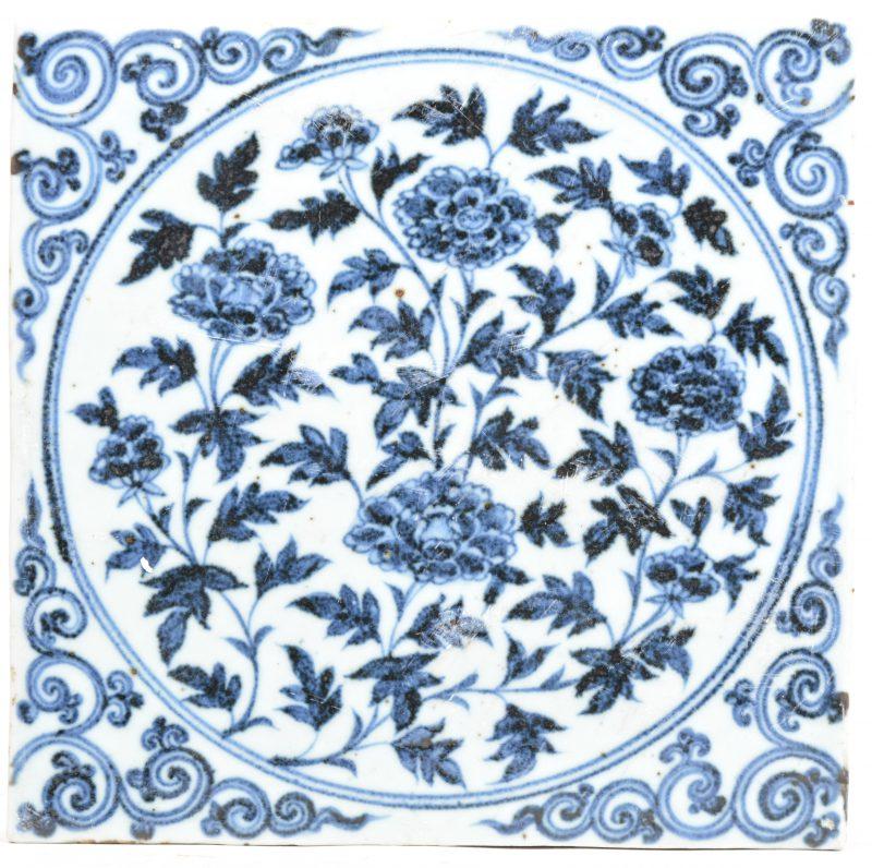 Een tegel van Chinees porselein met een blauw op wit bloemendecor.