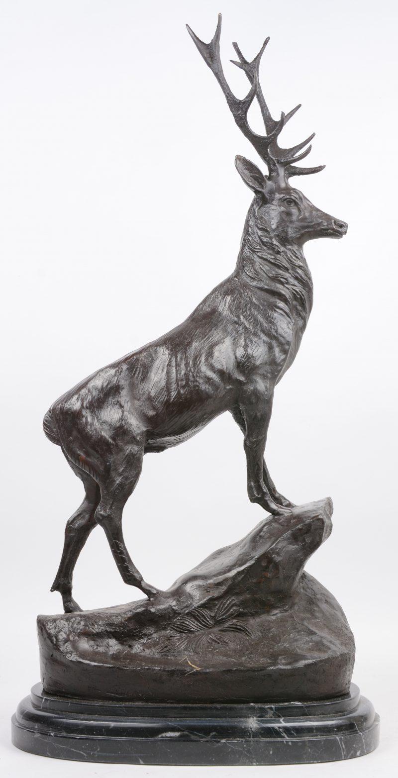 Een bronzen edelhert op zwart marmeren sokkel. Naar een werk van Jules Moigniez.