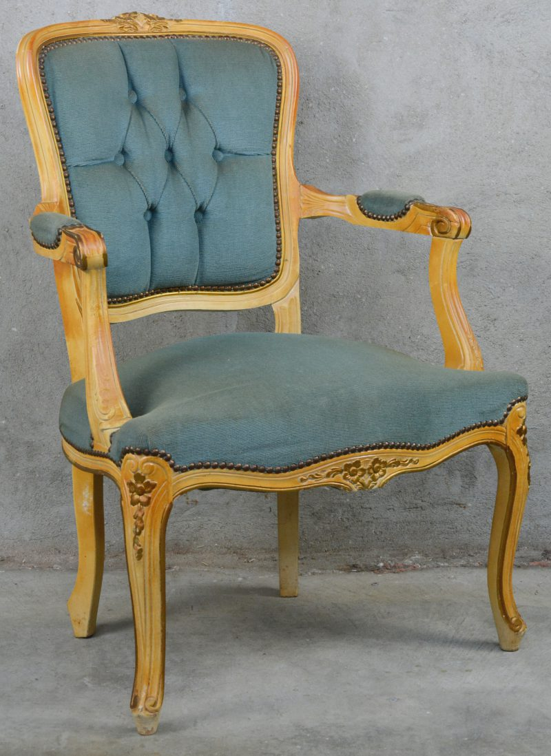 Een armstoel in Lodewijk XV-stijl met blauwe stoffen bekleding.