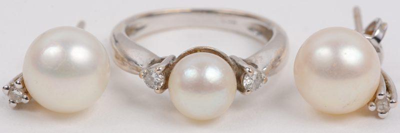 Een 18 karaats wit gouden ring met bijpassende oorbellen bezet met briljanten met een gezamenlijk gewicht van +- 0,10 ct. en drie parels.