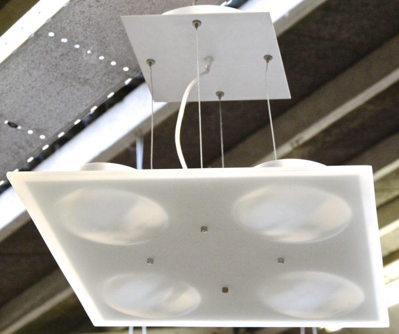 Een moderne plafonnière van mat glas met vier lichtpuntjes.