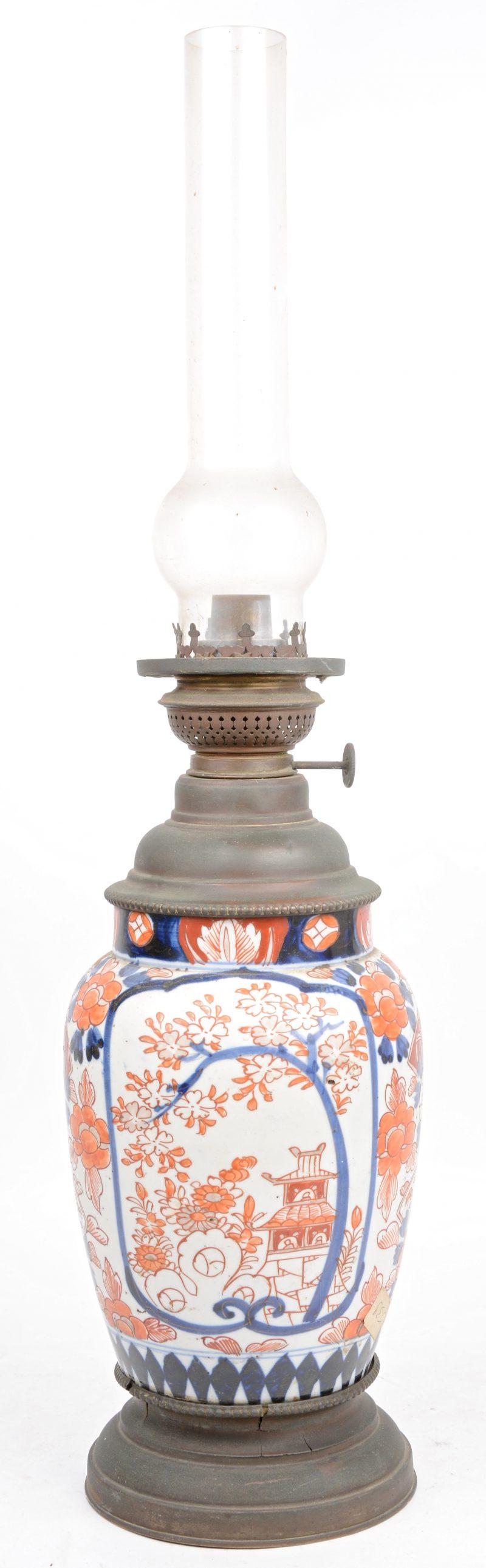 Een olielamp van Imari porselein en koper. Met lampglas. Omstreeks 1900.