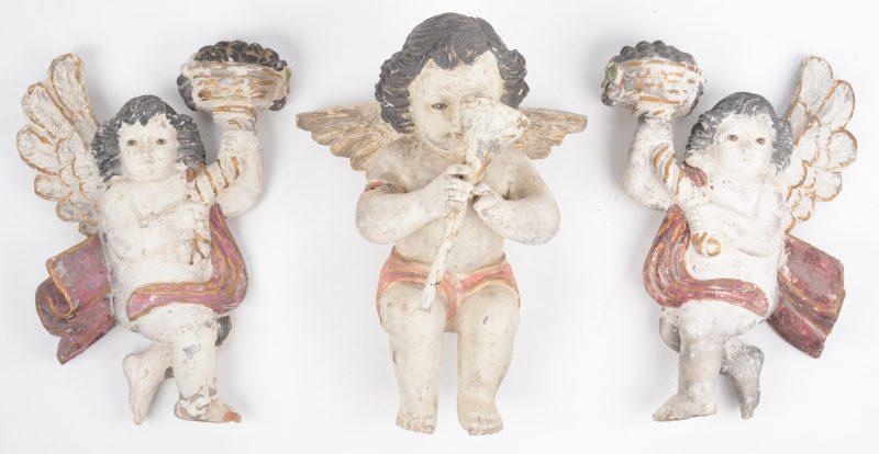 Drie gepolychromeerde houten engelen met glazen ogen.