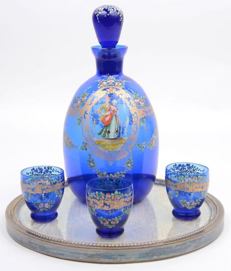 Een karafje en drie borrelglaasjes van blauw glas, versierd met handgeschilderd decor. Gepresenteerd op een rond schoteltje met kant tussen glas in verzilverd metalen montuur.
