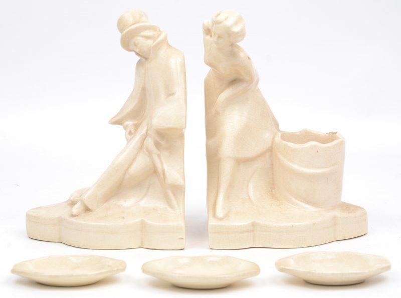 Een paar boekensteunen van monochroom wit aardewerk, ze stellen een man en een vrouw voor en vormen een rokersset met drie kleine losse asbakjes.