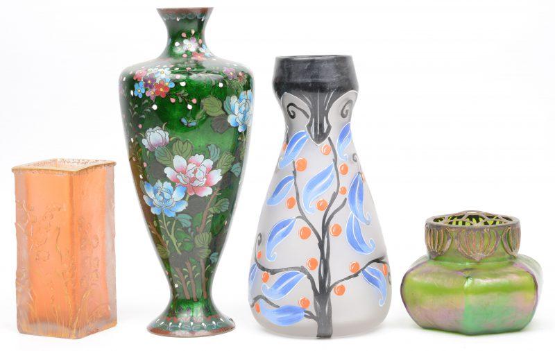 Vier diverse vaasjes. Een vierkant van glaspasta met meiklokjes, gemerkt Daum Nancy (H. 11,5 cm, schilfer aan de voet), een balustervormig met geëmailleerd bloemenmotief op messing, een van beschilderd opaline, gemerkt Novelty (H. 23 cm) en een kleine pique-fleurs van iriserend glas in de geest van Loetz.