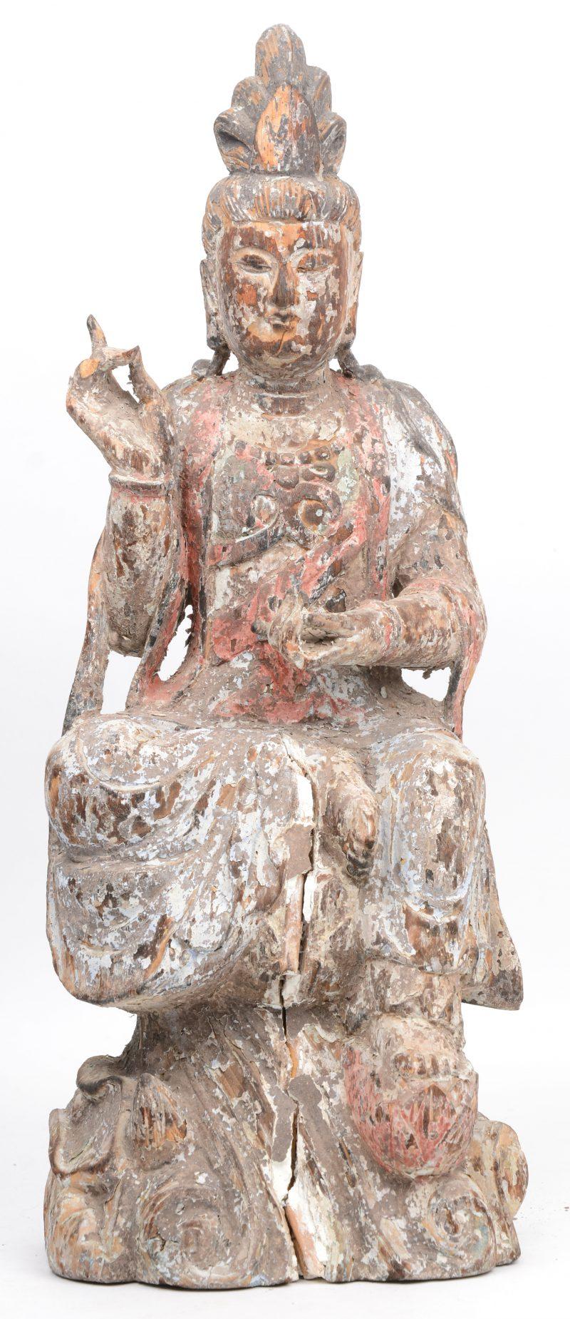 Een antiek houten Boeddhabeeld met sporen van polychromie en met opening in de rug. Op sokkel.