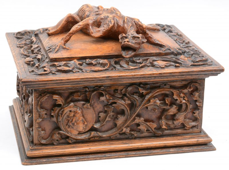 Een fijn uitgestoken juwelenkoffertje, versierd met bladermotieven rondom en het deksel getooid met een draak. (letsel aan binnenkant deksel).