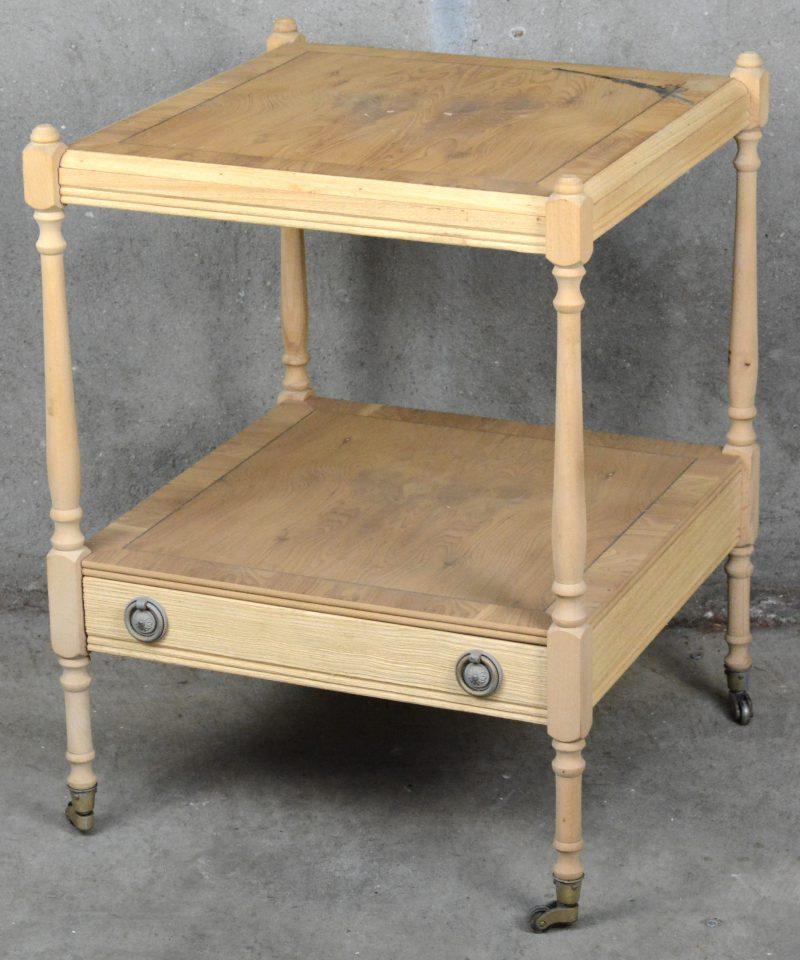 Een blank houten meubeltje met een lade in het tussenblad. Op wieltjes.