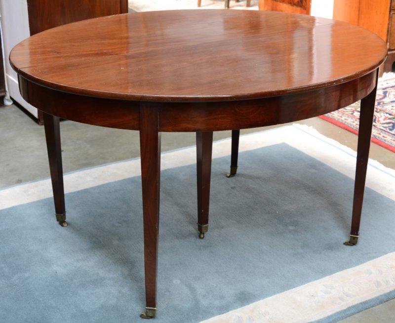Een ovale tafel van mahoniehoutfineer met vier tapse poten. XIXe eeuw.