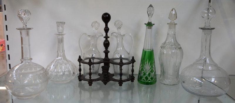 Een lot glaswerk, bestaande  uit vier verschillende kleurloze glazen karaffen, een kristallen karaf met groen decor en een glazen olie- en azijnstelltje in houten rekje.