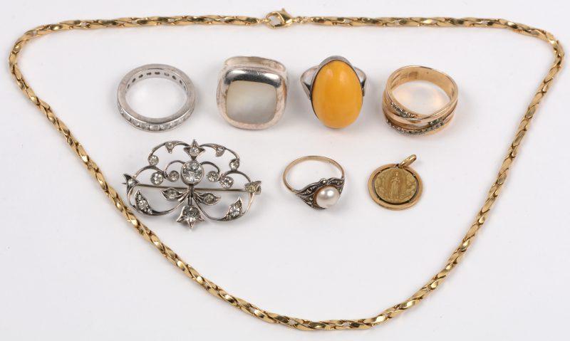 Drie verschillende zilveren ringen en een broche bezet met fantasiestenen. We voegen er een 9 karaats geel gouden ring met een parel en markasiet en een fantasie ring en ketting en hanger van Lourdes aan toe.
