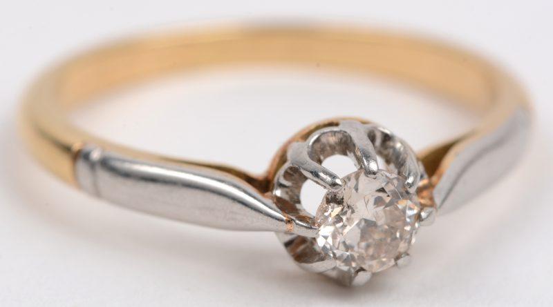 Een 18 karaats wit en geel gouden ring bezet met één briljant van +- 0,20 ct.